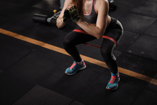 Cropped shot of a sportswoman doing glutes workout, squatting with resistance band at the gym