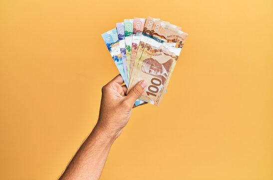 Hand of hispanic man holding canadian dollars over isolated yellow background.