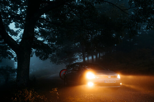 Asturias, Spain - September 9th 2020: A Volkswagen Golf VII with lights on being driven by a mountain path, with misty light, and entering into the forest, in Asturias mountain range, Spain.