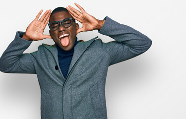 Young african american man wearing business clothes and glasses smiling cheerful playing peek a boo with hands showing face. surprised and exited Wall mural