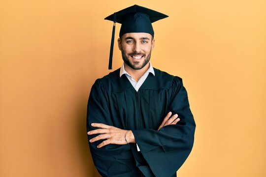 Young hispanic man wearing graduation cap and ceremony robe happy face smiling with crossed arms looking at the camera. positive person.