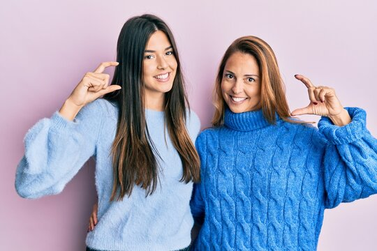 Hispanic family of mother and daughter wearing wool winter sweater smiling and confident gesturing with hand doing small size sign with fingers looking and the camera. measure concept.