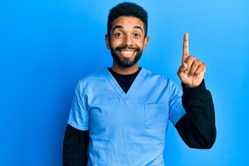 Handsome hispanic man with beard wearing blue male nurse uniform pointing finger up with successful idea. exited and happy. number one. Wall mural