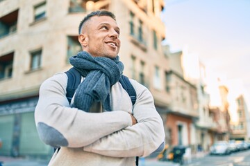 Fototapeta Young caucasian man smiling happy wearing backpack at the city.