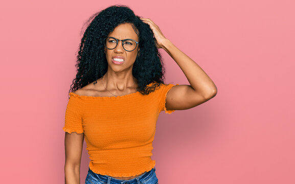Middle age african american woman wearing casual clothes and glasses confuse and wonder about question. uncertain with doubt, thinking with hand on head. pensive concept.