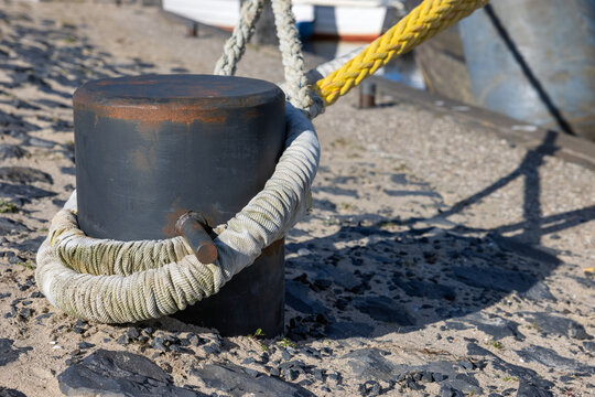 Steel bollard with tight ropes of moored ships