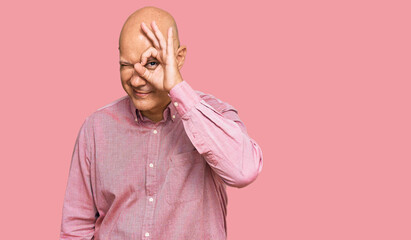 Fototapeta Middle age bald man wearing casual clothes doing ok gesture with hand smiling, eye looking through fingers with happy face.