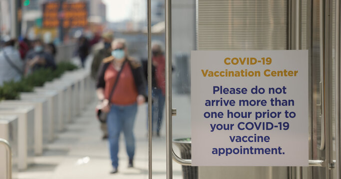 People walking into mass Covid 19 vaccination site place in New York City Javits Center