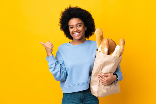 Young African American woman buying something bread isolated on yellow background pointing to the side to present a product