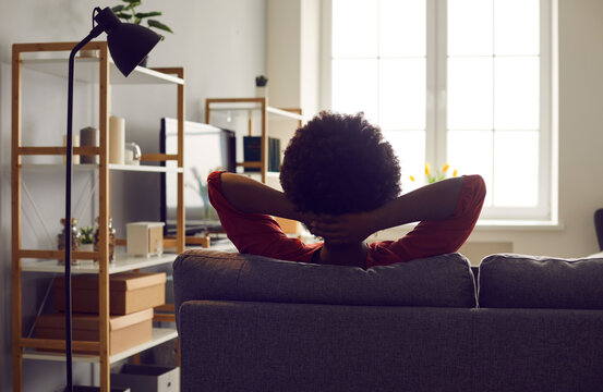 Spending peaceful weekend on comfortable couch at home. Happy relaxed African American woman sitting hands behind head on sofa feeling safe, looking out window, contemplating future, backlit back view