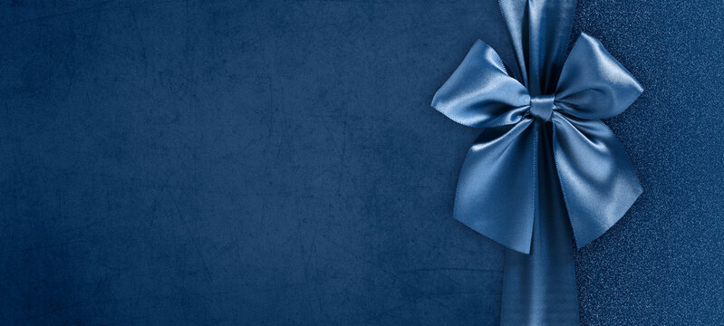 gift card with bright and shiny ribbon bow isolated on blue grunge background, top view and copy space template, layout useful for best wishes and shopping concept