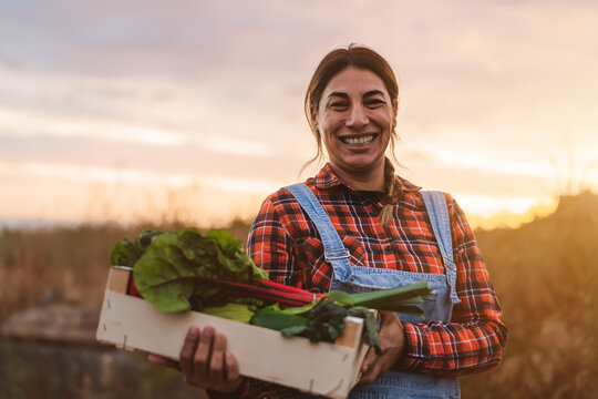 Happy female farmer holding a wood box containing fresh vegetables