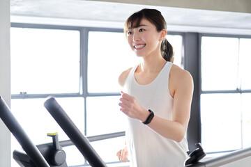 Fototapeta ランニングマシンで走るアジア人女性