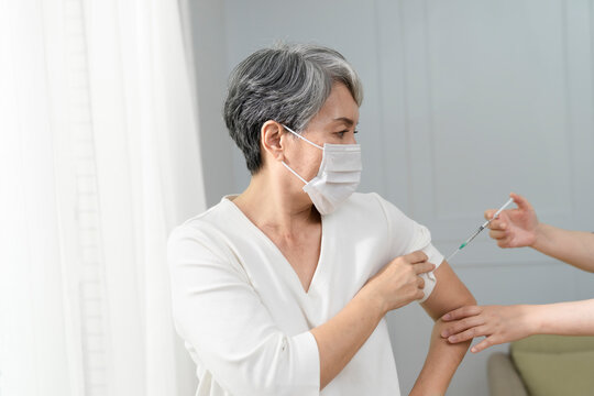 giving vaccine injection into senior woman shoulder