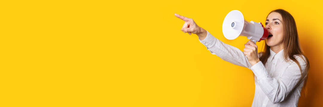 Young woman in a white shirt makes an announcement in a megaphone and points a finger on a yellow background. Hiring concept, help wanted. Banner