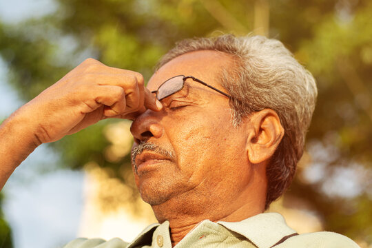 Head shot of worried senior old man rubbing his eyes - conept of healthcare, medical and stressed out elderly people