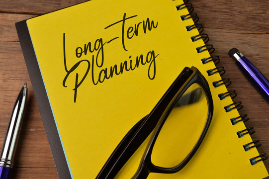 Top view of pen, eyeglasses and notebook written with LONG-TERM PLANNING
