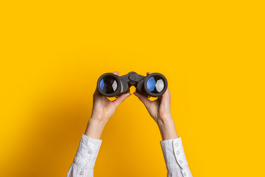 female hands hold black binoculars on a bright yellow background