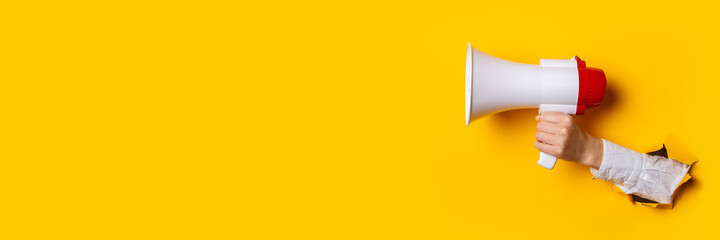 Hand holds a megaphone from a hole in the wall on a yellow background. Concept of hiring, advertising something. Banner