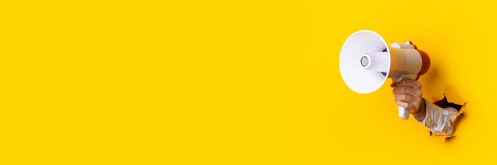 Obraz Hand holds a megaphone from a hole in the wall on a yellow background. Concept of hiring, advertising something. Banner - fototapety do salonu