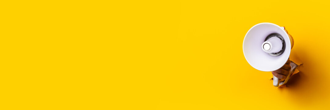 Female hand holding a megaphone from a hole in the wall on a yellow background. Concept of hiring, ad, discounts. Banner