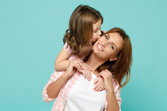 Happy woman in pink clothes have fun with child baby girl 5-6 years old Mommy little kid daughter stand behind hug kiss isolated on pastel blue azure background studio Mothers Day love family concept