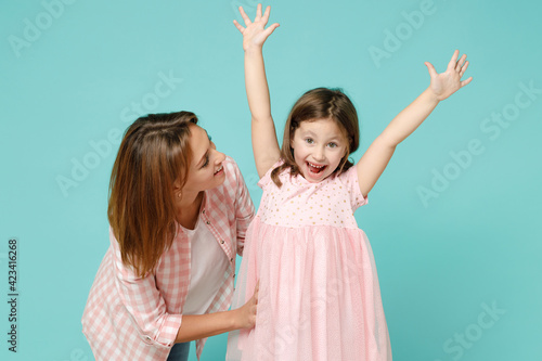 Happy woman in pink clothes have fun child baby girl 5-6 years old. Mommy little kid daughter doing winner gesture celebrate isolated on pastel blue background studio Mother's Day love family concept
