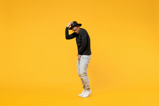 Full length young cool fashionable american african man 20s wearing stylish black hat shirt pants eyeglasses touching hat dancing have fun isolated on yellow orange color background studio portrait