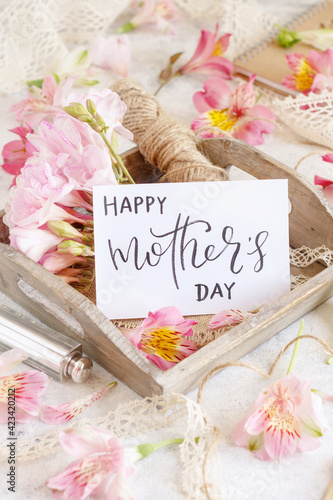 Happy Mother's Day handwritten card on a wooden tray between pink flowers