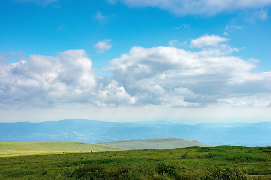 nature landscape of carpathian mountains. beautiful rolling scenery with grassy meadows in summer. clouds on the sky above the distant watershed ridge