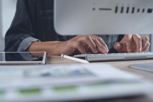 Man graphic designer working on desktop ocmputer and digital tablet in modern office