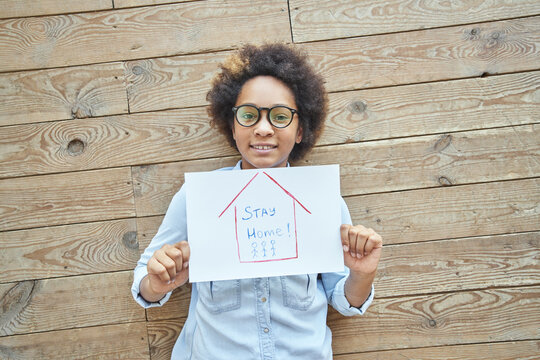 Mixed race teen girl holding drawing picture with words Stay Home while standing over wooden wall background. Social media campaign for coronavirus prevention