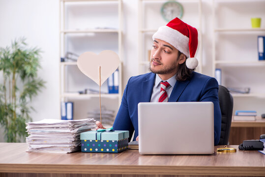 Young male employee working in the office at Christmas Eve