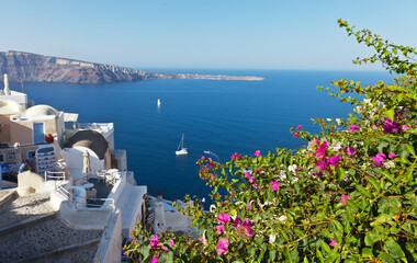 Greece. Santorini island. The beautiful village of Oia with bougainvillea flowers in narrow streets against backdrop of azure waters of the Aegean Sea on sunny day. Seascape. Summer holidays