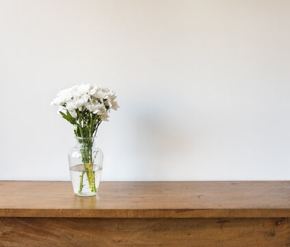 Close up of white chrysanthemums in glass vase on oak table against neutral background (selective focus)