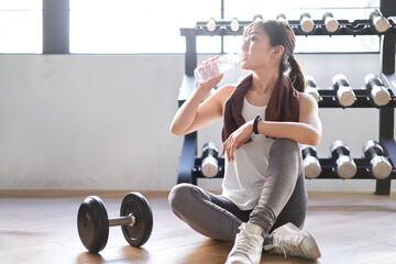 トレーニングジムで休憩をするアジア人女性