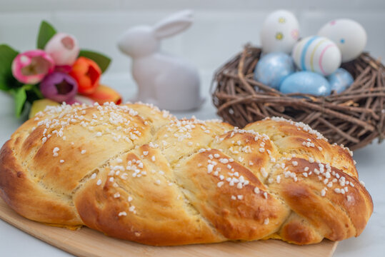 Sweet home made braided yeast bun for easter on a table
