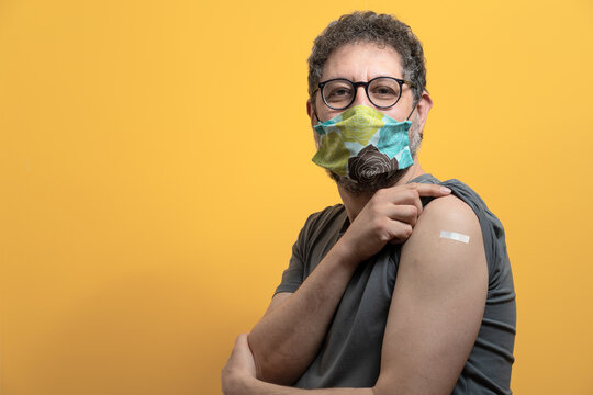 Senior man wearing face mask showing vaccinated arm. coronavirus vaccination concept of man received the corona virus vaccine.