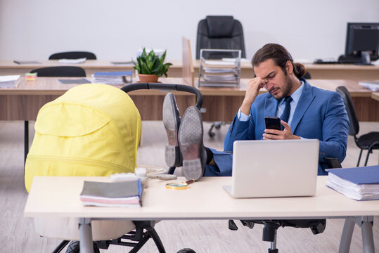 Young male employee looking after new born at workplace