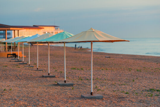 Row of beach umbrellas on a sandy beach by the sea in the morning