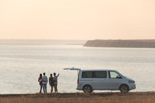The four friends standing near the minivan against the sunset sky
