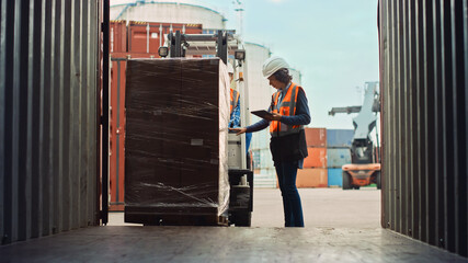Fototapeta Forklift Driver Loading a Shipping Cargo Container with a Full Pallet with Boxes in Logistics Port Terminal. Latin Female Industrial Supervisor and Safety Inspector with Tablet Managing the Process.