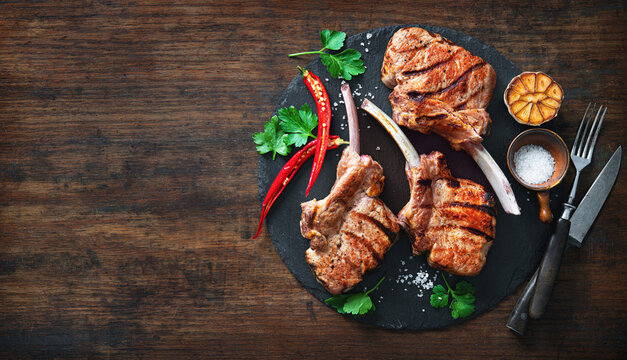 Grilled veal meat ribs cutlets with ingredients on wooden table