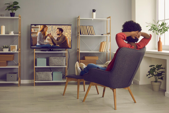 Woman relaxing in chair at home and enjoying television soap opera with a happy ending. Young lady sitting in comfortable armchair in living-room and watching romantic series or reality show on TV