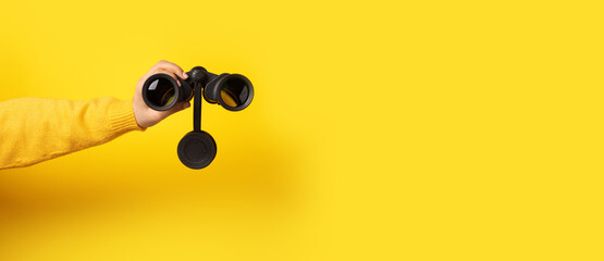 hand holding binoculars over yellow background, panoramic image - fototapety na wymiar