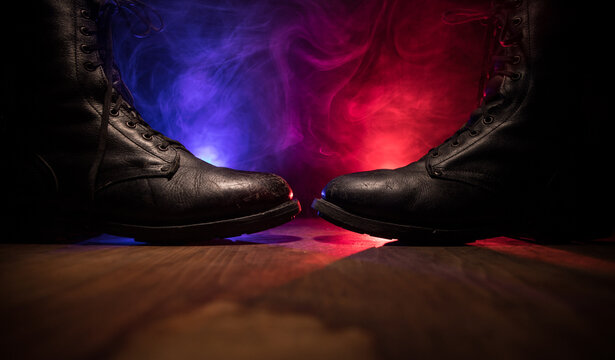 War concept. Old military shoe in a dark toned foggy background. Creative concept of conflict between countries, military aggression.