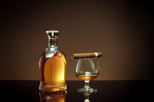 close up view of cigar, bottle of cognac and a glass aside on brown back.