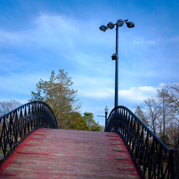 Steep Wooden Footbridge with Black Metal Railings and Tall Street Lamp against Blue Cloudy Sky. Weathered Red Painted Arching Wood Bridge over Pond at Elm Park in Worcester, Massachusetts.