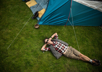 Relaxed man resting on a fresh, green lawn