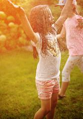 Joyful kids enjoying summer shower in the garden